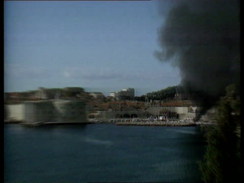 stockvideo's en b-roll-footage met split david chater wounded yugoslavia croatia dubrovnik lms old town harbour area and thick smoke seen zoom in explosions and smoke around boat in... - kroatië