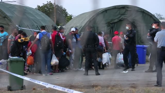 croatian authorities supervise refugees as they enter a camp near the croatian-serbian border in opatovac, croatia on wednesday, september 23, 2015... - 2015 stock-videos und b-roll-filmmaterial