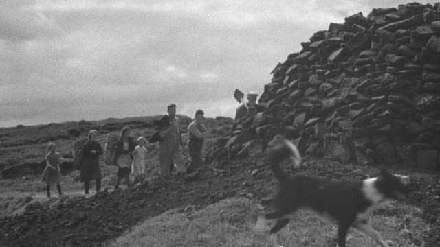 1944 pan crofter families setting off down dirt road to the peat with spade and shovel while discussing peat cutting rights in community / achriesgill, sutherlandshire, scotland - achriesgill stock videos and b-roll footage