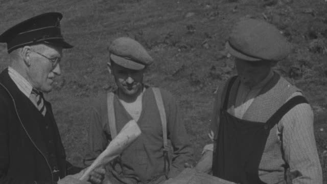1944 ts crofter receiving parcel and newspaper from postman then walking down dirt road with fellow crofter and dog / achriesgill, scotland, united kingdom - achriesgill stock videos & royalty-free footage