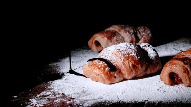 croissant baking with throwing sugaron black background - croissant stock videos & royalty-free footage