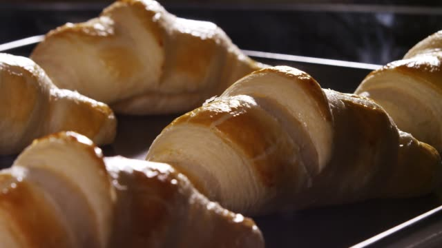 a croissant being baked and rising in the oven - french food stock videos & royalty-free footage