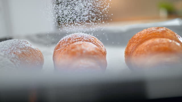 slo mo ld croissant being dusted with powdered sugar - cream cake stock videos & royalty-free footage