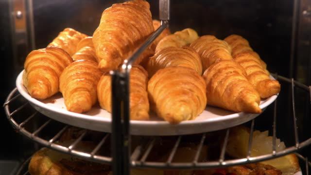 vídeos de stock, filmes e b-roll de pão de croissant no forno pronto para comer na linha de buffet do café da manhã do hotel. - crocante