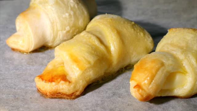 vidéos et rushes de doudoune croissants et pâtisseries juste sortis du four - aliment cru