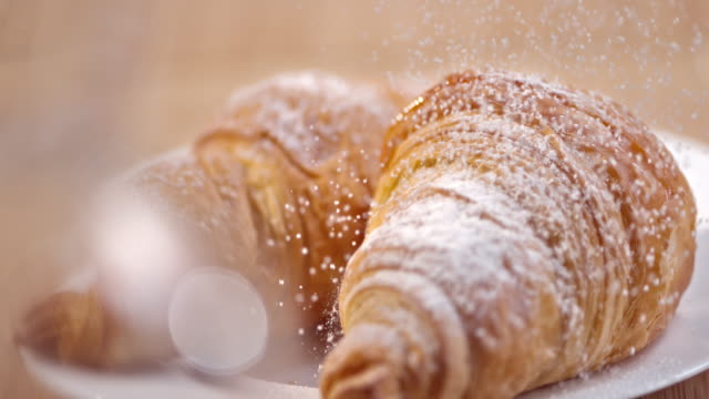slo mo croissants being sprinkled with sugar - french food stock videos & royalty-free footage