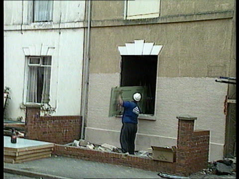 ENGLAND Gloucester Cromwell St MS Window frame as man knocks out bricks LMS Man lifting door out of window frame MS Man carrying door along BV...
