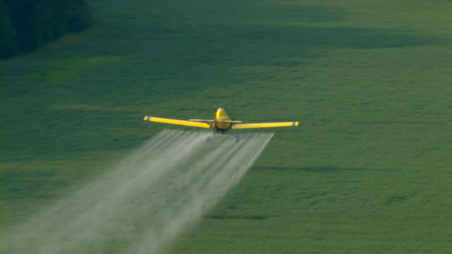 a crop duster distributes insecticide over farmlands in mississippi. - chemical stock videos & royalty-free footage