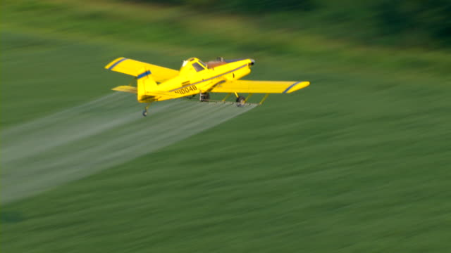 A crop duster distributes insecticide over farmlands in Mississippi.