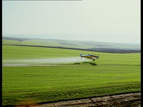 aerial ws side pov crop duster in action over fields, galilee, israel - insecticide stock videos & royalty-free footage