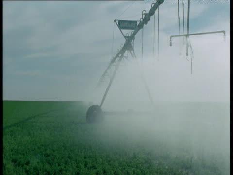crop sprayer moves across pivot irrigation field, arizona - irrigation equipment stock videos & royalty-free footage