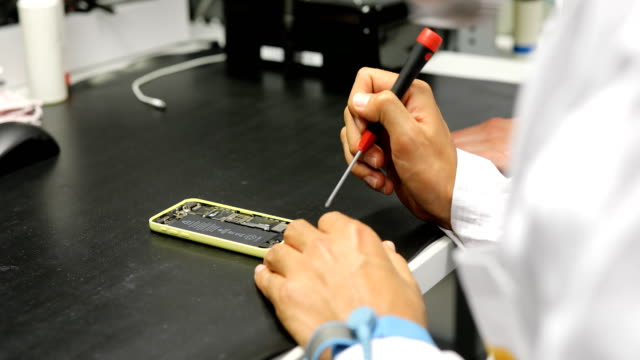 cropped hand of engineers repairing smart phone - electrical component stock videos and b-roll footage