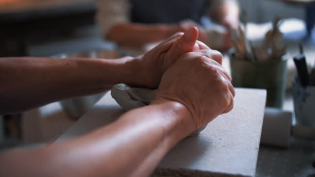 cropped hand of senior woman kneading clay in workshop - pottery stock videos & royalty-free footage