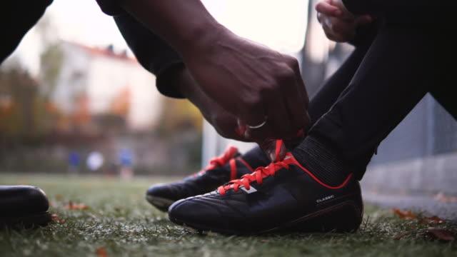 vídeos de stock, filmes e b-roll de cropped hands of grandfather tying shoelace of grandson sitting on soccer field - amarrar