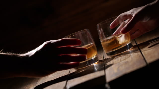cropped image of two men clanging glasses of alcoholic beverage together while sitting at bar counter in a modern urban cafe - scotch whiskey stock videos & royalty-free footage