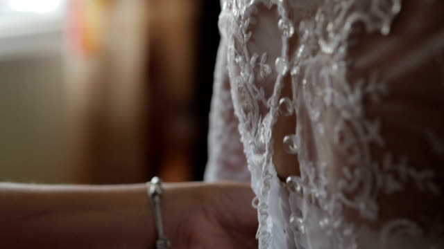 Cropped image of woman dressing up bride