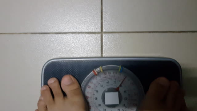 cropped image of woman feet standing on weigh scales - instrument of measurement stock videos & royalty-free footage