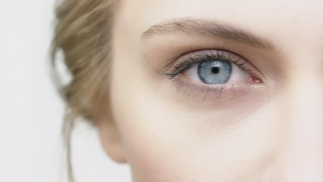cropped image of woman opening her blue eye - beautiful people stock videos & royalty-free footage