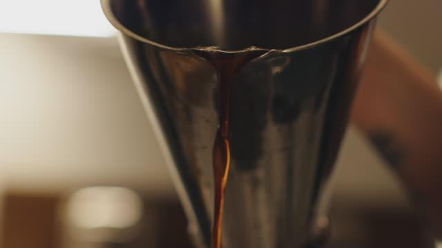 stockvideo's en b-roll-footage met bijgesneden beeld van werknemer gieten koffie in de fabriek - koffie drank