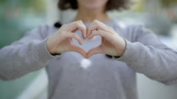 Cropped shot of woman making heart shape with hands