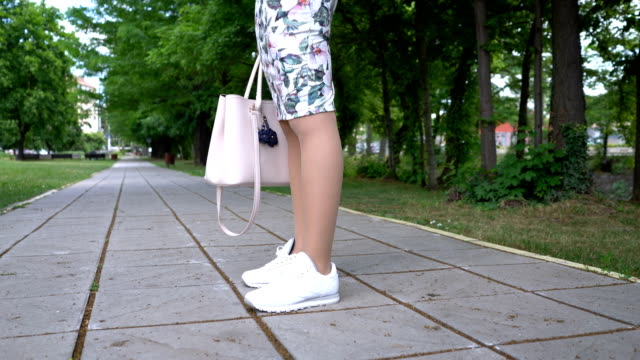 Cropped video footage of young woman standing at the park alley