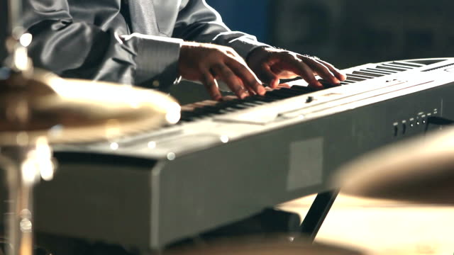 Cropped view of black man playing electronic keyboard