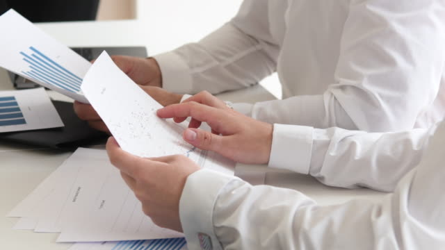 cropped view of businessmen holding paperwork, one man pointing at graph - graph paper stock videos & royalty-free footage