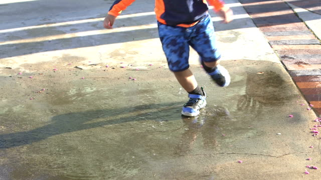 cropped view of little boy playing in puddle - sidewalk stock videos & royalty-free footage