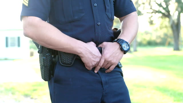 cropped view of police officer duty belt - ufficiale grado delle forze armate video stock e b–roll