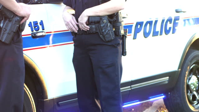 cropped view of police officers by squad car - police force stock videos and b-roll footage