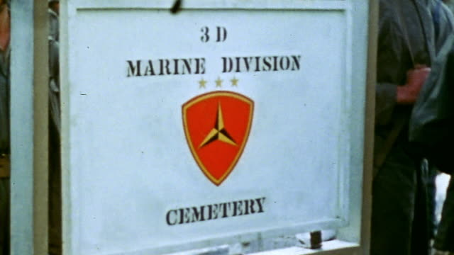 cross and plaque reading three of our buddies of the 3rd marine division carved in the ground 3rd marine division cemetery sign and marines filing... - battle of iwo jima stock videos and b-roll footage