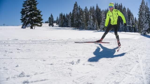 Cross country skier full power skate skiing uphill
