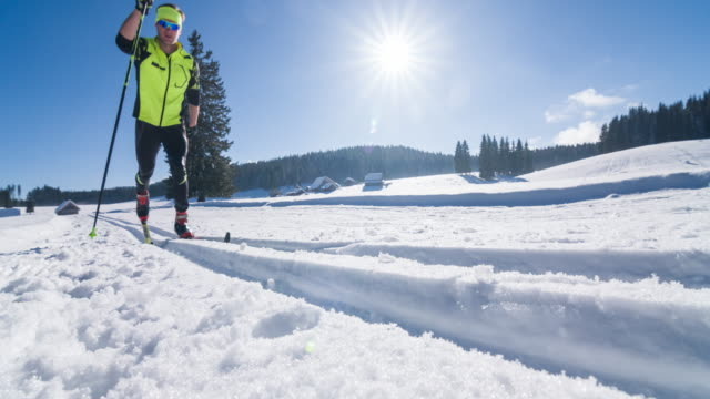 cross country skier gliding on skiing track in idyllic landscape - striding stock videos & royalty-free footage