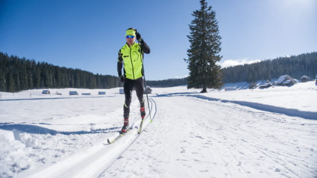 cross country skier gliding on skiing track in winter landscape - striding stock videos & royalty-free footage