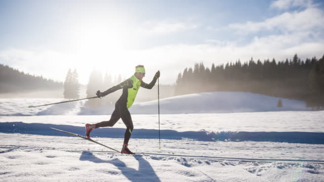 cross country skier gliding on skiing track in winter landscape - skiing and snowboarding stock videos and b-roll footage