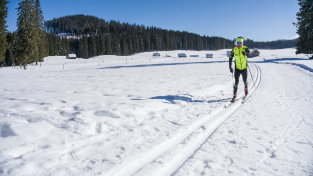 cross country skier gliding on skiing track in winter landscape - gliding stock videos and b-roll footage