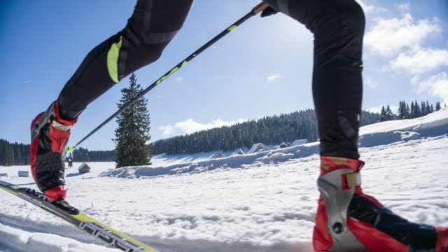 Cross country skier gliding on skiing track