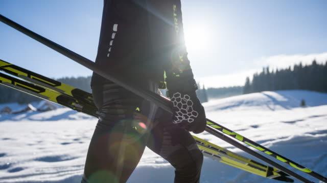 vídeos de stock e filmes b-roll de cross country skier in winter landscape carrying his sports equipment - bastão de esqui