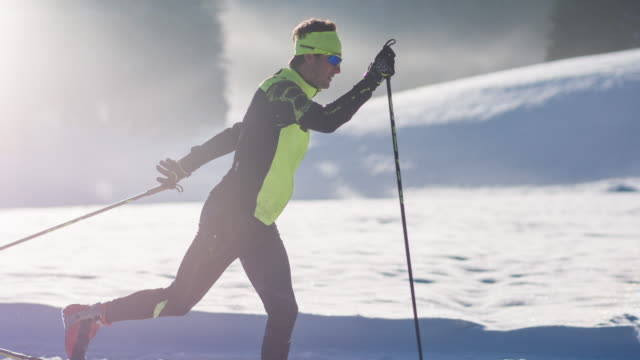 Cross country skier on skiing track in idyllic winter landscape