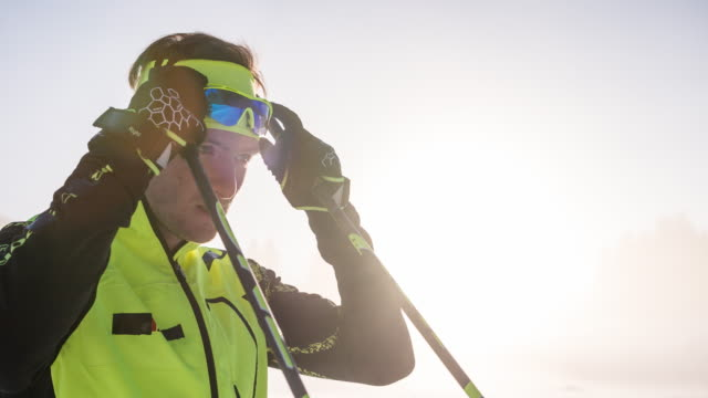 cross country skier putting on sunglasses, getting ready for competition - sci attrezzatura sportiva video stock e b–roll