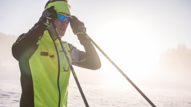 cross country skier putting on sunglasses, getting ready for competition - winter sports event stock videos and b-roll footage