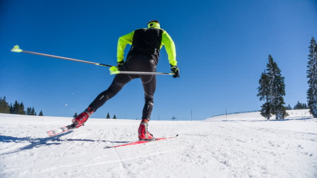 cross country skier skate skiing uphill on a snowy landscape - skiing and snowboarding stock videos and b-roll footage