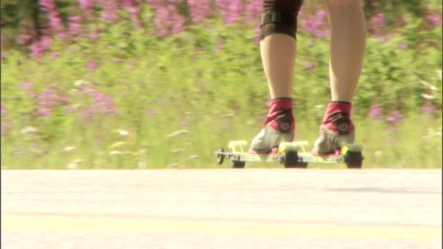 vídeos de stock e filmes b-roll de a cross country skier trains on roller skies. - bastão de esqui