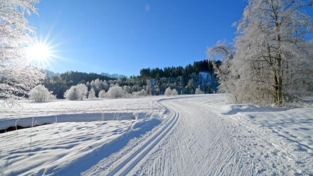 cross country skiing track with sun in winter landscape near lake barmsee, krün, garmisch-partenkirchen upper bavaria, bavaria, germany, european alps - krün stock videos and b-roll footage