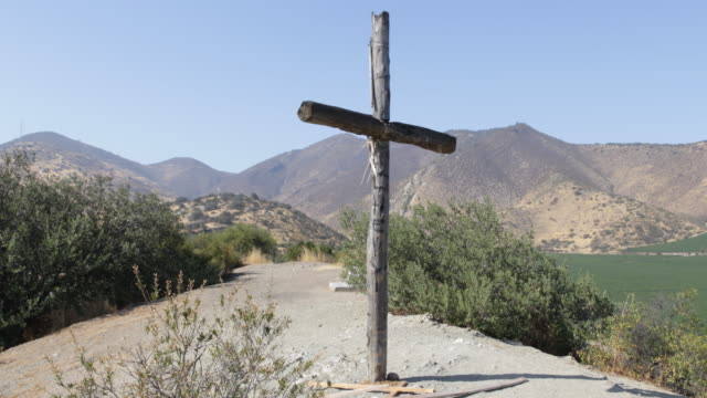 cross made of wood on a hill in a mountain landscape on a hill in the background another cross is visible in calera de tango chile calera de tango... - jesuit stock videos and b-roll footage