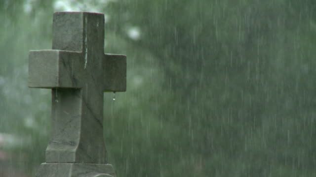 Cross on tombstone with heavy rain