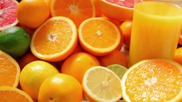 cu ds cross section of fresh oranges and glass of juice / london, united kingdom - inquadratura dall'alto di un tavolo video stock e b–roll