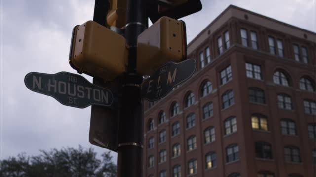 stockvideo's en b-roll-footage met cross street sign n. houston st. and elm st. with the texas school book depository in the background. dealey plaza, dallas, texas. - straatnaambord