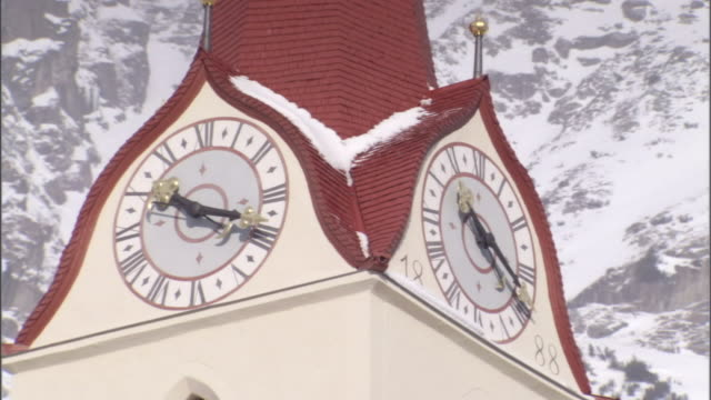 a cross tops a red spire on a clock tower. - spire stock videos & royalty-free footage