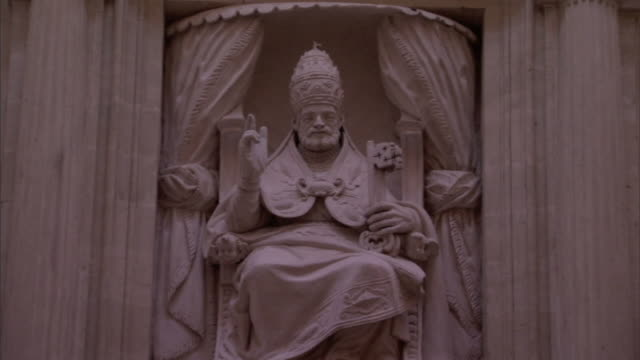 a cross tops the roof of a temple housing a statue of a religious leader sitting on a throne. - ペディメント点の映像素材/bロール